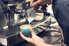 Young african american barista in eyeglasses pointing at screen while working at coffee shop. 7 Free Best Online Coffee Barista Courses Certificates 2021