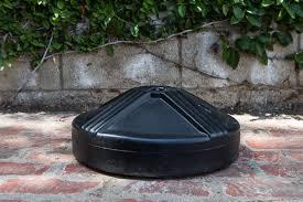 the us weight umbrella base sitting on a brick patio