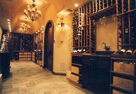a barrel vaulted ceiling and arched entry define this highly styled cellar a hanging stemware rack over the sink a waterfall display counter level