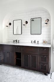 a beautiful arch shape frames the white tile wall above this double vanity