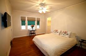 middle bedroom with refinished original hardwood floors and a walk in closet with built in chest of drawers tv stays