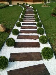 simple white stones with reclaimed teak wood walway path ideas and green garden landscape