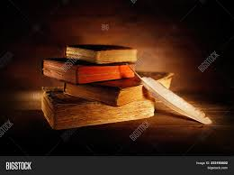 old books with quill pen on wooden table