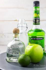 straight on shot of all the ings needed to make a sour apple tequila l