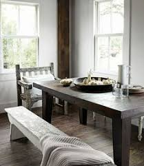 rustic white dining room in this northern california home s dining room a smith hawken chair and two wooden benches provide seating at a table that the