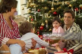 Family In Pajamas Giving Gifts On Christmas Stock Photo  Getty ImagesGiving Gifts On Christmas