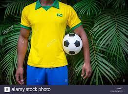 Il calcio brasiliano player in bandiera Brasile e colori uniformi in  permanente palm frond giungla tropicale tenendo palla calcio Foto stock -  Alamy