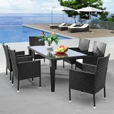 gray plastic wicker outdoor dining room set with glass dining table and chairs having short black