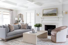 a steel gray sofa accented with pink and gray pillows sits in an elegant living room on a white and silver rug facing a cream waterfall coffee table matched