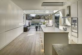 trendy contemporary kitchen in white adds to the appeal of the reved house