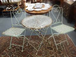 a wrought iron patio set with circular folding table and two chairs painted pale green