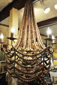 this gorgeous gold gilded metal light fixture with intricate faded wooden beads outlining