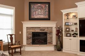 electric corner fireplace with natural blend ledgestone and painted wood surrounding trim with raised hearth