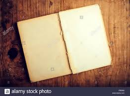 top view of old open book with blank pages on wooden desk as copy e retro toned image