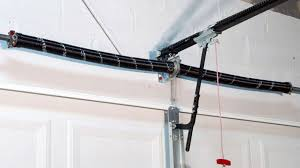 broken garage door springs a long black coiled spring is shown above the top of the inside of a closed