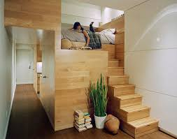 a wooden loft bed in a tiny apartment