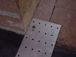 in this job where 3 8 holes were drilled in the masonry hearth and header to accept masonry anchors a 3 8 hole is drilled in the plate 1 2 from the jamb