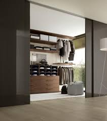 cozy master bedroom walking closet space ideas chest of drawer wall hook shelves quilt tempered glass sliding door arch lamp wooden floors