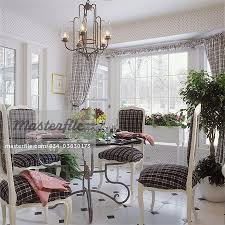 dining room round glass table with scroll iron base french style side chairs painted white wood upholstered in black and white plaid bowl of fruit