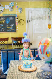 Baby Boy Wearing Party Hat With First Birthday Cake At Table Stock