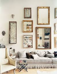 casually elegant with multiple mirrors as a gallery wall i love the fringe trim sofa photo source domino