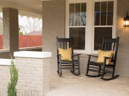 farm house black pine wood rocking chair which s up with orange cushions front porch