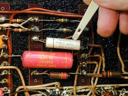replacing capacitors in old radios and tvs use your ering iron to melt the er on the terminal suck the excess er from the terminal and use your thin pliers to remove the snipped wire