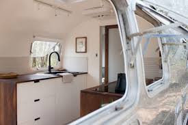 The wood and clean lines of the interior contrast with the Airstream's  sleek, silver exterior
