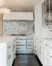 contemporary kitchen features a pair of ochre arctic pear chandelier hangs over an island accented with a white waterfall countertop