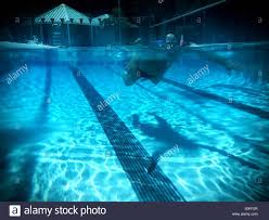 swimmer viewed simultaneously above and below water in an outdoor 25 meter olympic size swimming pool