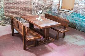 narrow solid wood distressed trestle dining table with benches with back for rustic farmhouse dining room design with exposed brick wall ideas