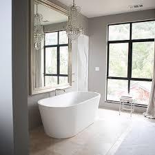 white and gray bathroom with paris flea market chandelier over bathtub