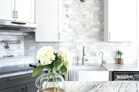 white kitchen countertops two toned gray and white cabinets marble subway tile a white kitchen cabinets