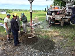 the marblehead light department helps the conservancy trail crew install granite gate posts at lead mills