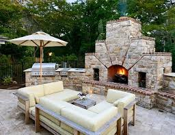 stone fireplace next to the outdoor kitchen and a lovely lounge by bruce palmer