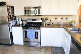 Styled brown oak floating shelves are stacked over a coffee station placed atop a white and gray quartz countertop accenting white cabinets with satin nickel knobs. We Painted Our Kitchen Cabinets Benjamin Moore Swiss Coffee The Fitnessista