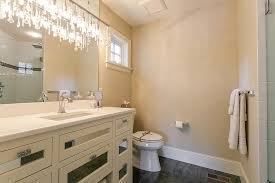 fabulous powder room boasts a crystal linear chandelier hanging over a white washstand with mirrored drawers alongside a gray tiled floor