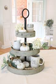 3 tiered wooden stand filled with harvest decorations as a centerpiece on a dining table