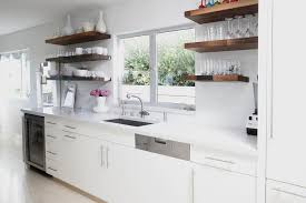 white kitchen with wood floating shelves