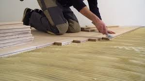 4k00 16carpenter worker installing wood parquet construction in a renovated room installation of parquet