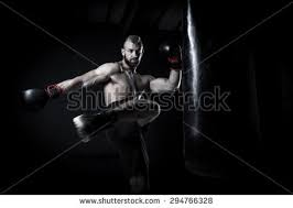 dramatic studio lighting. male athlete boxer punching a bag with dramatic edgy lighting in dark studio t
