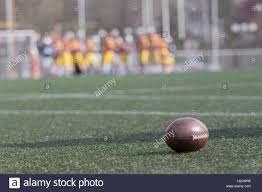 grass american football field. Ball On Green Grass American Football Field And Blurred Players In The Background