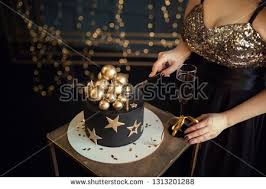 Portrait Of Pretty Woman Holding A Birthday Cake And Blowing Out The