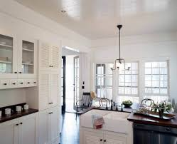 Louvered Cabinet Doors In The Kitchen In White Color With Apron Sink