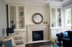glass doors wall unit painted white wall unit to the sides of fire place