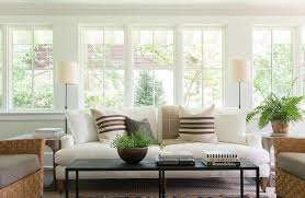 oil rubbed bronze floor lamps sit behind gray wood end tables placed flanking a white 2 cushion sofa accented with vintage burlap striped pillows and