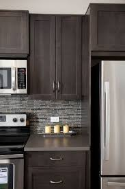 grey mosaic tile backsplash. kitchen- brown maple shaker-style cabinets, stainless steel microwave, stove and fridge with glass mosaic tile backsplash at prospect rise calgary townhomes grey e