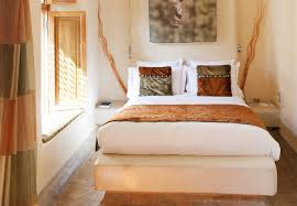 this africa inspired bedroom has light walls and various shades of ocher used for decor african inspired furniture