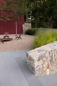 chunky stone wall with grasses and gravel area.