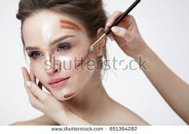 woman face makeup closeup of hands applying contouring and highlighting lines on female skin